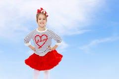 Kleines Mädchen in einem roten Rock und Bogen auf ihrem Kopf Lizenzfreie Stockfotos