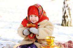Kleines Mädchen in einem russischen trinkenden Tee des Pelzmantels und des roten Schals an lizenzfreies stockbild