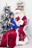 Kleines Mädchen in einem schönen blauen Kleid sitzt auf einem Schoss am Saint Nicolas Lizenzfreie Stockfotos