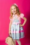 Kleines Mädchen in einem schönen Kleid mit einer Tasche Stockbilder