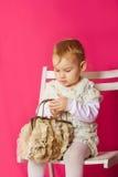 Kleines Mädchen in einem schönen Kleid mit einer Tasche Lizenzfreies Stockbild