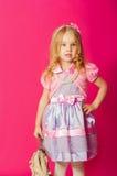 Kleines Mädchen in einem schönen Kleid mit einer Tasche Lizenzfreie Stockfotos