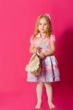 Kleines Mädchen in einem schönen Kleid mit einer Tasche Stockbild