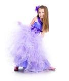 Kleines Mädchen in einem schönen purpurroten Kleid stockfotografie