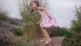 Kleines Mädchen in einem Sommerkleid, das einen Berg von Steinen klettert stock footage