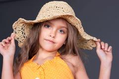 Kleines Mädchen in einem Strohhut, Studio Stockfotografie