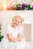 Kleines Mädchen in einem weißen Kleid, das am Weihnachtsbaum sitzt Stockfotografie