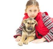 kleines Mädchen in einer roten Weste und in einem Welpen auf a Stockbild