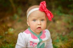 Kleines Mädchen in einer weißen Klage mit einem roten Bogen Stockfotos