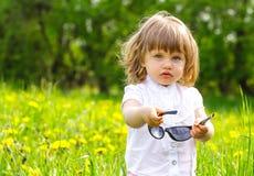 Kleines Mädchen in einer Wiese mit Sonnenbrillen stockfoto
