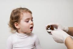 Kleines Mädchen erwartet ihre Medikation, die in einen Löffel gießt Stockfotografie
