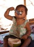 Kleines Mädchen essen Kokosnuss Lizenzfreie Stockbilder