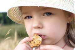 Kleines Mädchen essen Plätzchen auf dem Freilicht lizenzfreies stockfoto