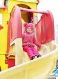 Kleines Mädchen fährt unten von einem Dia auf den Spielplatz draußen Lizenzfreie Stockfotos