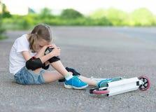 Kleines Mädchen fiel vom Roller lizenzfreie stockfotografie