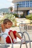 Kleines Mädchen, freier Sommertag, der im Lehnsessel sitzt Lizenzfreies Stockfoto