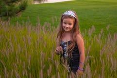 Kleines Mädchen geht auf dem Gebiet, im Park, nahe dem See, moderne Prinzessin, mit Krone, Glück, Sonnenuntergang Stockfotografie