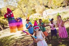Kleines Mädchen geht brach den Pinata für ihren Geburtstag Lizenzfreies Stockbild