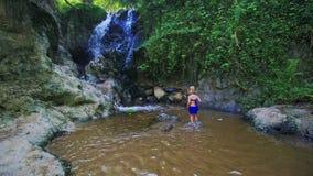 Kleines Mädchen geht in Flusswasser zum Wasserfall stock video
