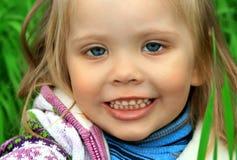 Kleines Mädchen geht im Früjahr auf ein junges Gras Lizenzfreie Stockfotografie