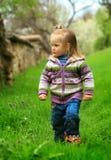 Kleines Mädchen geht im Früjahr auf ein junges Gras Stockbild