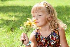 Kleines Mädchen genießt den Geruch der Blumen Stockfotos