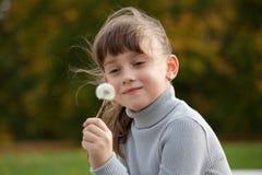 Kleines Mädchen genießt flaumigen Löwenzahn Lizenzfreie Stockbilder