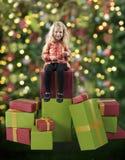 Kleines Mädchen gesetzt auf Weihnachtsgeschenken stockbilder
