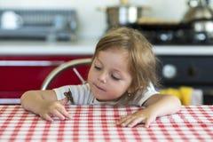 Kleines Mädchen hält auf der Hand den Schmetterling Aglais io und passt für ihn auf, Lizenzfreie Stockbilder
