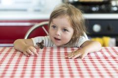 Kleines Mädchen hält auf der Hand den Schmetterling Aglais io und passt für ihn auf Stockfotos