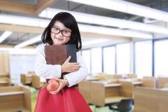 Kleines Mädchen hält ein Buch und einen Apfel Lizenzfreies Stockfoto