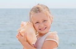 Kleines Mädchen hält ein Shell an Stockfotografie
