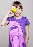 Kleines Mädchen hält einen Tennisball nahe dem Auge Lizenzfreies Stockfoto