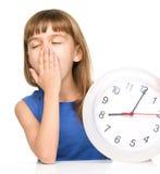 Kleines Mädchen hält große Uhr Stockfoto