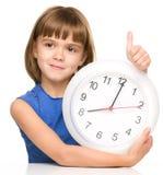 Kleines Mädchen hält große Uhr Stockbilder
