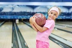 Kleines Mädchen hält Kugel im Bowlingspielklumpen an Stockfoto
