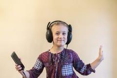 kleines Mädchen hört Musik auf einem Smartphone und tanzt stockfotografie