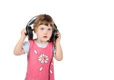 Kleines Mädchen hört Musik in den großen Kopfhörern Lizenzfreies Stockfoto