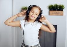 Kleines Mädchen hört Musik durch Kopfhörer Das Konzept von stockfoto