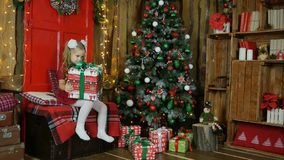 Kleines Mädchen hat ein neues Jahr ` s Geschenk gefunden Sie ist glücklich Lizenzfreie Stockfotos