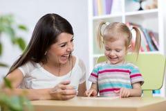 Kleines Mädchen hat Puzzlespiel gelöst Glückliche Mutter, die ihre Tochter betrachtet lizenzfreie stockfotografie