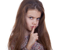 Kleines Mädchen hat Zeigefinger zu den Lippen als Zeichen der Ruhe gesetzt Lizenzfreies Stockfoto