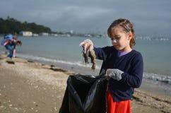 Kleines Mädchen heben Abfall vom Strand auf stockfotos