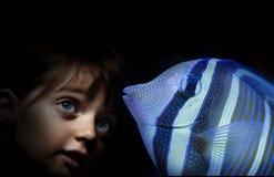 Kleines Mädchen hinter dem Aquarium, das auf Fischen schaut Lizenzfreies Stockfoto