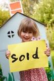 Kleines Mädchen-Holding verkaufte Zeichen außerhalb des Spiel-Hauses Stockfoto