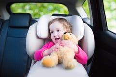 Kleines Mädchen im Auto-Sitz Stockfoto