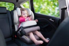 Kleines Mädchen im Auto-Sitz Stockfotos