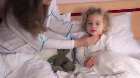 Kleines Mädchen im Bett, das Gesundheits-Check-Kinderarztdoktorkontrollkopf und -kehle hat stock video