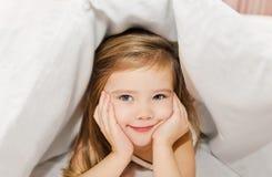 Kleines Mädchen im Bett unter Abdeckung Lizenzfreie Stockbilder