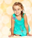 Kleines Mädchen im blauen Kleid auf ihren Knien Stockbild